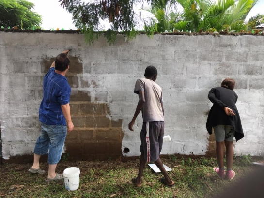 White washing a wall whilst volunteering in Africa